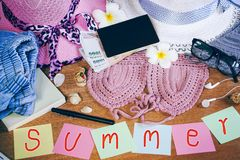 Holidays or summer concept background with girl accessories bikini,hat,money,passport and paper currency on wooden table. Preparing to travel Stock Photo