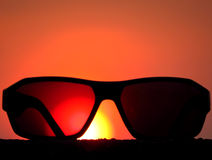 Holidays Sunglasses. A metaphorical picture of sunglasses against the backdrop of the setting sun conceptualizing a holiday Stock Images