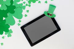 Tablet pc and st patricks day decorations on white. Holidays and technology concept - tablet pc computer and st patricks day decorations made of paper on white Stock Photos