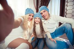 Holidays, technology and people concept - happy family sitting on floor and taking selfie picture with smartphone at. Home, in a winter sweater and hat, the Stock Photo