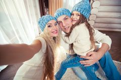 Holidays, technology and people concept - happy family sitting on floor and taking selfie picture with smartphone at. Home, in a winter sweater and hat, the Stock Photography