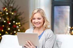 Woman with tablet pc at home on christmas stock image