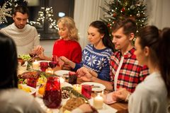 Friends having home christmas dinner and praying. Holidays and thankfulness concept - friends holding hands and praying while having christmas dinner at home stock images