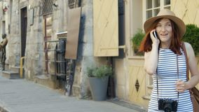 Holidays and tourism - beautiful girl with phone, tourist book and vintage camera in the city. Holidays and tourism - beautiful red head girl with phone, tourist stock video footage