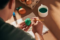 Holidays, tradition and people concept - close up of man hands coloring easter eggs with brush.  royalty free stock photo