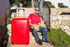 Holidays, travel, people concept - young man sitting on stairs with suitcases.  royalty free stock image