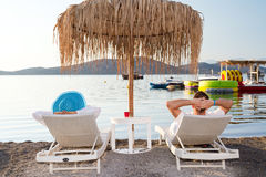 Holidays under parasol in Greece. Couple on holidays under parasol in Greece Royalty Free Stock Photo