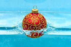 Holidays and vacation concept. Festive decoration for Christmas tree, red ball with glitter decor dropped into water. Blue background. Christmas decoration or stock photography