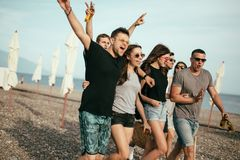 Holidays, vacation. group of friends having fun on beach, walking, drink beer, smiling and hugging. Best friends. Group of young people walking on beach, drink royalty free stock photos