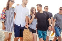 Holidays, vacation. group of friends having fun on beach, walking, drink beer, smiling and hugging. People Group of best friends or students On Beach. Summer stock photography