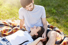 Holidays, vacation, love and friendship concept. Couple in love resting together on green grass of meadow, looking each other in e royalty free stock image
