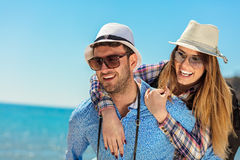 Holidays, vacation, love and friendship concept - smiling couple having fun. Over sky background Stock Image
