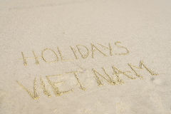 Holidays Vietnam written in sand. Holiday Vietnam written on the sand in Danang beach, Vietnam Royalty Free Stock Photography