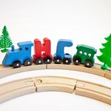 Holidays, winter and celebration concept - Christmas composition Russian wooden letters train cars the word New Year on wood railw. Ay fir tree and white stock photography