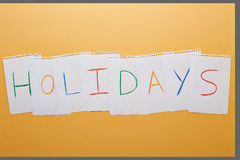 Holidays word written on notebook pages Royalty Free Stock Photos