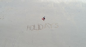 `Holidays` written in the sand on the beach and back of the woman laying on the towel. Travel holiday concept Royalty Free Stock Photos