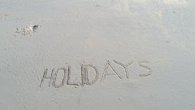 `Holidays` written in the sand on the beach. Travel holiday concept Royalty Free Stock Photos