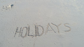 `Holidays` written in the sand on the beach. Travel holiday concept Royalty Free Stock Photography