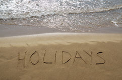 Holidays written in sand Stock Image