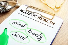 Holistic health and words mind, body and soul. Clipboard with Holistic health and words mind, body and soul stock photos