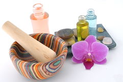 Holistic spa. Orchid, wooden mortar and pestle, healing stones and botanical bottles, ready for you beauty needs Royalty Free Stock Image
