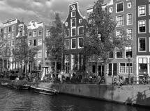 Holländarehus i Amsterdam längs en kanal under sommaren Arkivfoto