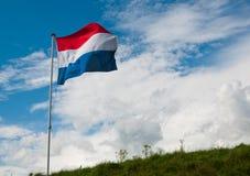 Holländische Staatsflagge, die in den starken Wind wellenartig bewegt Lizenzfreies Stockfoto