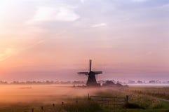 Holländische Windmühle im Nebel im frühen Morgen Stockfotografie