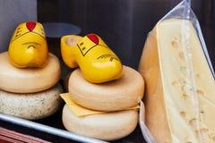 Holländischer Käse und traditionelle hölzerne Schuhe verstopft im Shopfenster stockfotos