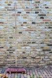 Holländischer roter Besen im Fall gegen eine historische Wand Stockfotos