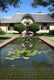 Holländisches Haus des Umhangs hinter reflektierendem Teich Stockfotos