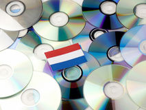 Holländsk flagga överst av CD- och DVD-högen som isoleras på vit royaltyfri bild