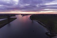 Holländsk flod med dramatisk solnedgång Royaltyfri Bild