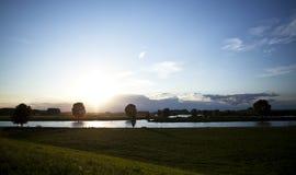 Holländsk himmel och flod på solnedgången Fotografering för Bildbyråer