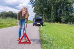 Holländsk kvinna som förlägger varningstriangeln på den lantliga vägen Fotografering för Bildbyråer