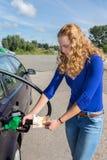 Holländsk kvinna som tankar bilbehållaren med bensin Arkivbild