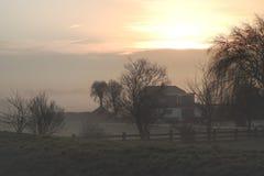 Holländsk lantgård på soluppgång på en dimmig vintermorgon royaltyfria foton