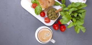 Holländsk lunch med en smörgås och ett doftande kaffe Nytt bröd med mazarellaost, körsbärsröda tomater, pestosås och basilika fotografering för bildbyråer