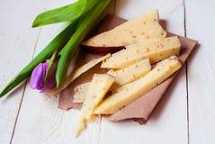 Holländsk ost med bockhornsklöver och valnötter på en trätabell med en tulpan Arkivbild