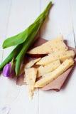 Holländsk ost med bockhornsklöver och valnötter på en trätabell med en tulpan Arkivbilder
