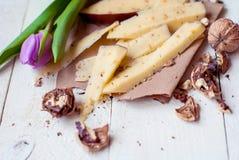 Holländsk ost med bockhornsklöver och valnötter på en trätabell med en tulpan Fotografering för Bildbyråer