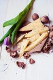 Holländsk ost med bockhornsklöver och valnötter på en trätabell med en tulpan Royaltyfria Foton