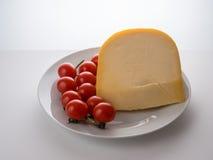 Holländsk ost och små tomater Arkivfoto