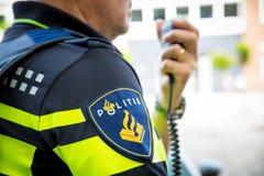 Holländsk polis med radion Fokus på emblem med logo royaltyfria foton