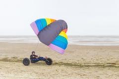 Holländsk tonårs- pojke som kör barnvagnen med draken på stranden royaltyfri bild