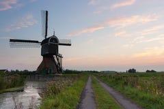Holländsk väderkvarn på solnedgången Royaltyfria Bilder