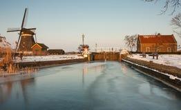Holländsk winterlandscape med väderkvarnen och slussen Arkivfoton