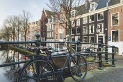 Holländska kanalhus med cykeln som lutar mot bron royaltyfri foto