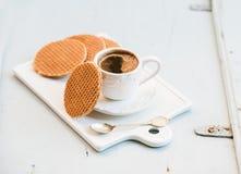Holländska karamellstroopwafels och kopp av svart kaffe på det vita keramiska portionbrädet över ljus - blå träbakgrund Royaltyfria Foton