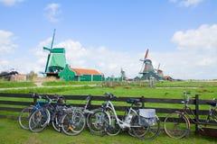 Holländska väderkvarnar med cyklar i Zaanse Schans Royaltyfri Fotografi